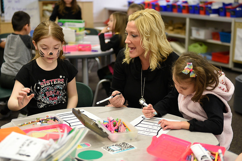 BEN MIKESELL | THE GOSHEN NEWS Kindergarten teacher Jami Brouillette, center, instructs Jordyn Grant, left, how to color her hat in class Wednesday morning at Concord East Side Elementary School.