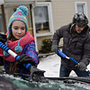 "BEN MIKESELL | THE GOSHEN NEWS<br /> Lily Fournier, 12, of Goshen, works with her father Cory to scrape ice off his car Tuesday morning on Wilson Avenue in Goshen. ""We just moved from Arizona, so this is still fun for us,"" Cory said."