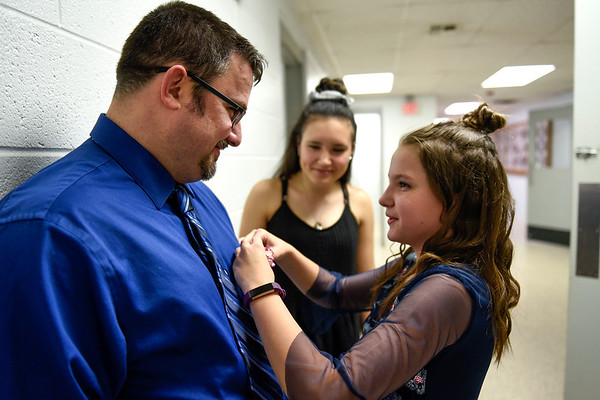 BEN MIKESELL | THE GOSHEN NEWS<br /> Chelsea Duncan, 12, right, places a flower in her father Jeremy Duncan's pocket while her sister Allie, 15, watches during the Daddy Daughter Dance Wednesday night at the Elkhart County 4-H Fairgrounds.