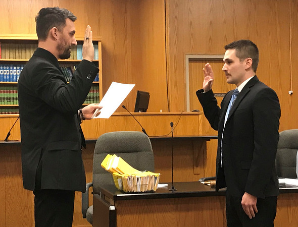 JOHN KLINE | THE GOSHEN NEWS<br /> Goshen Mayor Jeremy Stutsman, left, conducts the swearing-in ceremony for Tyler J. Thibodeaux following his hiring as a probationary firefighter with the Goshen Fire Department during the Goshen Board of Public Works and Safety meeting Monday afternoon.