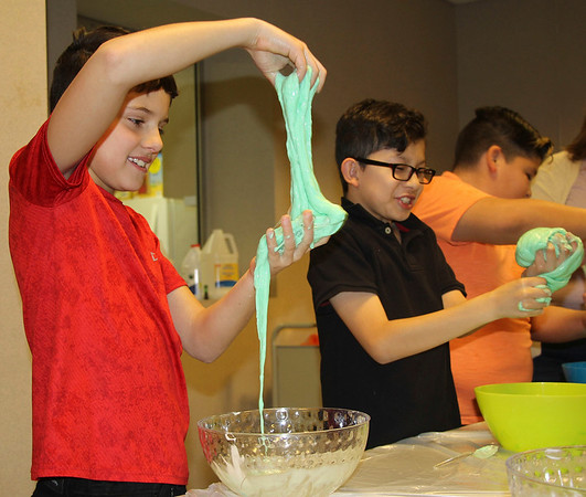 """JOHN KLINE   THE GOSHEN NEWS<br /> Lucas Alvarez-O'Connell, 10, left, and Itzae Juarez-Arreola, 10, both of Goshen, try their hand at making """"Jabba Slime"""" during the Evil Genius: Star Wars program at the Goshen Public Library Monday afternoon."""