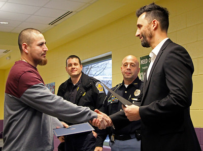 GEOFF LESAR | THE GOSHEN NEWS  Juan Alvarez, left, of Goshen, shakes hands with Goshen Mayor Jeremy Stutsman as Assistant Chief Shawn Turner, back left, and Chief Jose Miller of the Goshen Police Department look on Thursday evening at the Boys & Girls Club in Goshen. Alvarez was one of four citizens, multiple GPD officers and Goshen Community Schools employees recognized Thursday for their handling of a Dec. 5 stabbing of a woman outside the Club and its aftermath. After witnessing an altercation in a vehicle, Alvarez said he was able to pull the suspect out of the vehicle by his feet. During a struggle to subdue the suspect, Alvarez said he was stabbed twice before the suspect fled on foot to a nearby vacant house, where he was later apprehended.