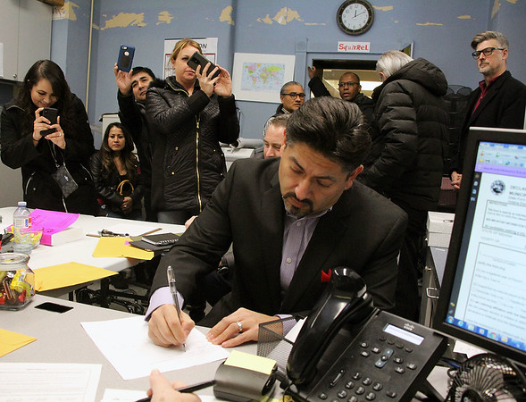 Roger Schneider | The Goshen News<br /> Republican candidate for the Goshen City Council 3rd District primary Felipe N. Merino, signs his candidacy Friday af the Elkhart County Clerk's Office while family and friends capture pictures of the event.