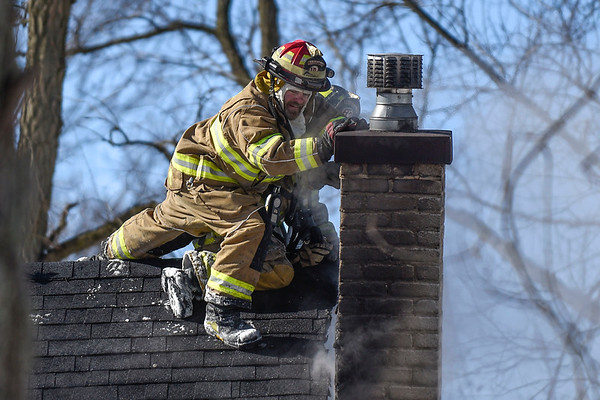BEN MIKESELL | THE GOSHEN NEWS Harrison Township firefighters work to push over the chimney while responding to a house fire at 57863 S. 7th St. in Elkhart.