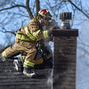 BEN MIKESELL | THE GOSHEN NEWS<br /> Harrison Township firefighters work to push over the chimney while responding to a house fire at 57863 S. 7th St. in Elkhart.