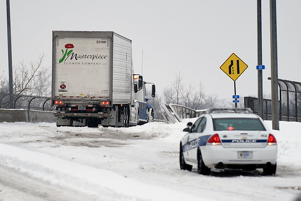 BEN MIKESELL | THE GOSHEN NEWS<br /> Goshen Police stopped traffic on the Ind. 15 overpass Monday afternoon after a semi was unable to make it up the snowy incline. The day's snowfall slowed traffic across northern Indiana.