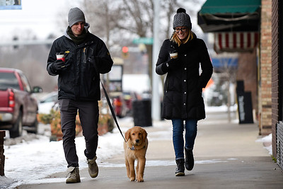 BEN MIKESELL | THE GOSHEN NEWS Taylor Wright, left, and Sarah Ober, right, both of Goshen, walk down Main Street with their dog Jack Thursday in downtown Goshen. While temperatures Thursday reached a high of 24 degrees, Friday is expected to be much colder with a high of 7 degrees and wind chill values as low as -20, according to the National Weather Service.