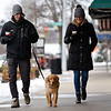 BEN MIKESELL | THE GOSHEN NEWS<br /> Taylor Wright, left, and Sarah Ober, right, both of Goshen, walk down Main Street with their dog Jack Thursday in downtown Goshen. While temperatures Thursday reached a high of 24 degrees, Friday is expected to be much colder with a high of 7 degrees and wind chill values as low as -20, according to the National Weather Service.