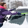 BEN MIKESELL | THE GOSHEN NEWS<br /> Emma Dugger, of Goshen, wipes off her windshield Monday morning on Fifth Street in Goshen. A travel advisory was in effect in Elkhart County throughout Monday as snow fell through the region.