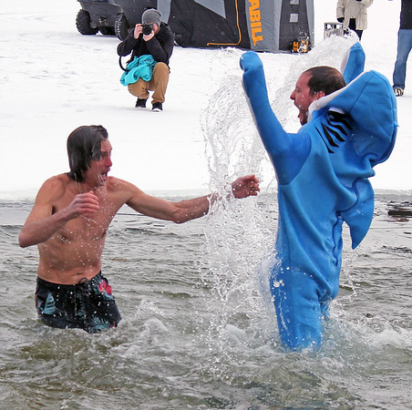 Roger Schneider | The Goshen News<br /> Ryan Bouillon of Syracuse lets out a victory whoop as Charles Harris looks on, after they dove into the frigid water of Lake Wawasee Saturday. Bouillon was wearing a shark suit to add to the fun. They and eight others participated in the Polar Plunge at Oakwood Inn to raise money for the Turkey Creek Fire Territory. The town's revived Winterfest, sponsored by Lakeland Youth Center, was also held at Oakwood Saturday.