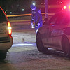 Roger Schneider | The Goshen News<br /> A Goshen police officer places crime scene evidence markers on West Washington Street Wednesday night. A car chase ended on West Washington just west of Third Street.