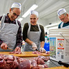 BEN MIKESELL | THE GOSHEN NEWS<br /> Volunteers, from left, Dick Steffen, New Paris, Kent Schreck, Goshen, and Gary Gill, Goshen, cut turkey meat at their work station Tuesday afternoon at The Depot in Goshen. The annual canning event, organized by the Mennonite Central Committee began Monday and will continue until Jan. 17. Normally 80,000 pounds of turkey are packaged during the nine-day span, Stanley Pletcher, chairman of the MCC Meat Canning Committee said. volunteers are welcome each day.