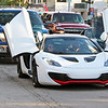 Roger Schneider | The Goshen News<br /> The driver of this McLaren supercar swings open the car's doors while slowly driving down Main Street in Goshen Friday night.