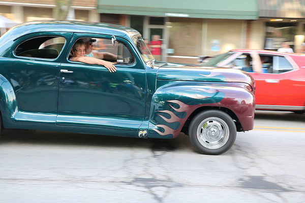 Roger Schneider | The Gosen News<br /> A couple cruises down Goshen's Main Street Friday night in their vintage car featuring flames on the fendes.