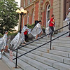 CAMDEN CHAFFEE | THE GOSHEN NEWS<br /> A group of rally participants don solar blankets to illustrate the treatment of immigrants at the U.S. - Mexico border.