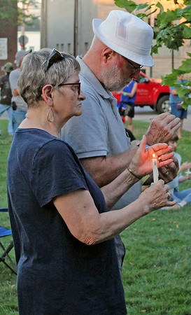 CAMDEN CHAFFEE | THE GOSHEN NEWS<br /> Margaret Sawatasky holds a candle as she stands next to her husband Friday night at the lights 4 liberty rally at the county courthouse in Goshen.