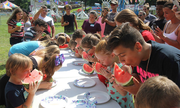 AIMEE AMBROSE | THE GOSHEN NEWS <br /> A table full of children chomp into watermelons while competing in the kids watermelon eating contest during the Bristol Homecoming Festival at Congdon Park Saturday.