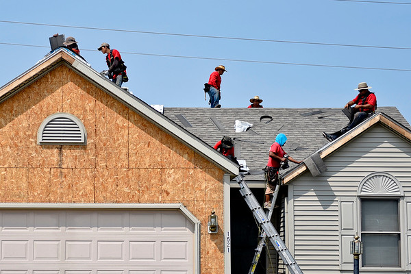 BEN MIKESELL | THE GOSHEN NEWS<br /> Employees of A&M Home Services out of Plymouth work on the roof of a house July 8 on Clover Creek Lane in Goshen.
