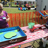 "AIMEE AMBROSE | THE GOSHEN NEWS <br /> Gwendalynn Gall, 5, Goshen, launches a toy frog into a box while playing the ""Frog Flipper"" game in the kiddie section of the Bristol Homecoming Festival at Congdon Park Saturday."