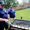 AIMEE AMBROSE | THE GOSHEN NEWS <br /> (from left) Firefighters AJ Robertson and Daniel Kurtz grill burgers at the Bristol Fire Department's booth during the Bristol Homecoming Festival at Congdon Park Saturday. The department sold the burgers as a fundraiser to help purchase new equipment.