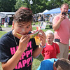 AIMEE AMBROSE | THE GOSHEN NEWS <br /> Aaron Angelmeyer, 12, of Goshen, bites into a watermelon while competing in the watermelon eating contest during the Bristol Homecoming Festival at Congdon Park Saturday. Angelmeyer finished his melon first to win the contest's trophy in the kids division.