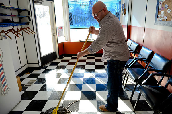 BEN MIKESELL | THE GOSHEN NEWS<br /> After the morning rush, Rob Drake mops the floor of his barber shop in Bristol.