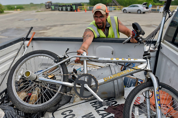 BEN MIKESELL | THE GOSHEN NEWS<br /> Elkhart County Landfill employee pulls a Diamondback bicycle out of his truck that was found in the garbage July 3.