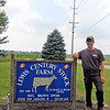 CAMDEN CHAFFEE | THE GOSHEN NEWS<br /> LaGrange dairy farmer and 4-H leader, Riley Lewis, stands out by his family's dairy farm sign on Wednesday July 3.