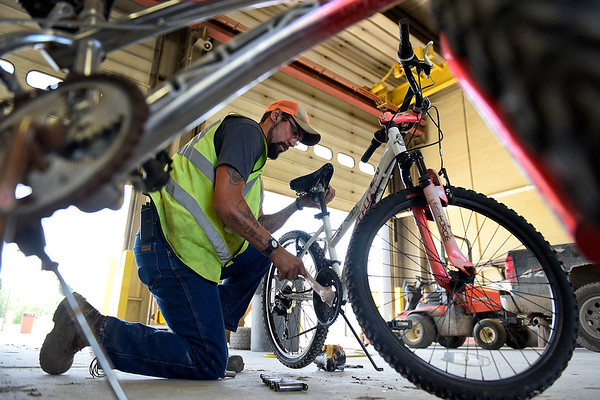 BEN MIKESELL | THE GOSHEN NEWS<br /> Beeson works on replacing the chain and gear mechanics on a bicycle Monday in the Elkhart County Landfill garage. He finds and restores bikes thrown out at the landfill, which he provides to people in the work release program for transportation.