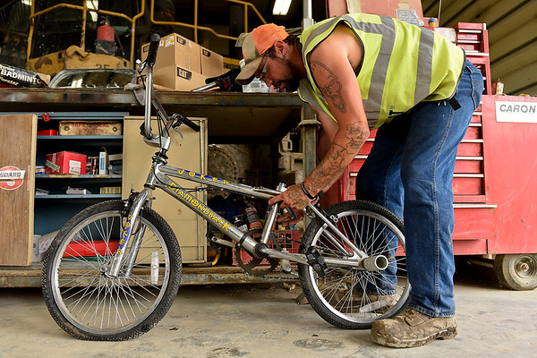 BEN MIKESELL | THE GOSHEN NEWS<br /> Elkhart County Landfill works on a Diamondback bicycle during his lunch break July 3 at the landfill. He restores bikes he finds at the landfill and gives them to people in the county-wide work release program.