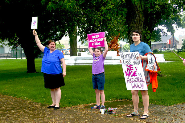 SHEILA SELMAN | THE GOSHEN NEWS<br /> From left, Jenifer Eisenhour, Syracuse, her daughter Coraline Eisenhour and Emily Klug hold signs  in support of abortion rights Saturday evening on the Elkhart County Courthouse lawn.