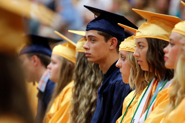 SHEILA SELMAN | THE GOSHEN NEWS<br /> Tanner Schlichter, center, listens to his classmates speak during commencement Sunday afternoon at Fairfield Jr.-Sr. High School.