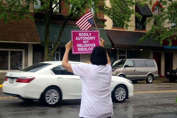 SHEILA SELMAN | THE GOSHEN NEWS<br /> Emily Tibbs of New Paris, holds a sign advocating abortion rights as traffic passes by along Main Street in downtown Goshen Saturday evening.
