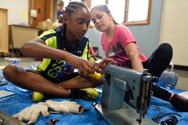 BEN MIKESELL | THE GOSHEN NEWS<br /> Fourth-graders Layla Evans, left, and Penelope Jimenez work to take apart a sewing machine Thursday during Bright Time Summer Camp week at Bethany Christian Schools. This station, called Breaker Space, allowed students to take apart various machines to learn how they work, then putting components together to try and make something new.