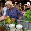 BEN MIKESELL | THE GOSHEN NEWS<br /> Kate Lind, of Three Rivers, Michigan, helps a customer from her table Saturday morning at the Goshen Farmer's Market. Kate and her husband James started their booth, Sustainable Greens, when the Farmer's Market opened 20 years ago.
