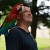 BEN MIKESELL | THE GOSHEN NEWS<br /> Scott Reinhart stands with his macaw Merlin as he tries to coax his new cockatoo Cheeto out of a tree Tuesday afternoon in Millersburg.