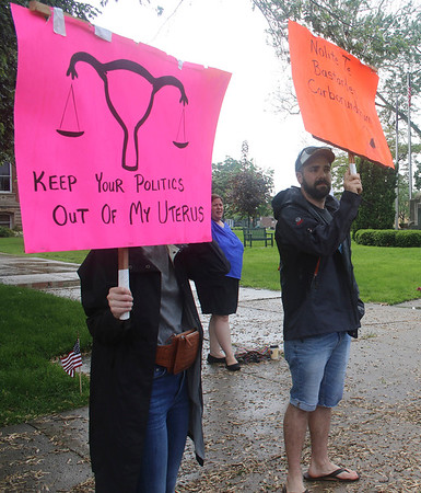 "SHEILA SELMAN | THE GOSHEN NEWS<br /> Malinda Wobrock, Goshen, left, holds a sign that reads, ""Keep your politics out of my uterus,"" at an abortion rights rally on the Elkhart County Courthouse lawn Saturday evening."