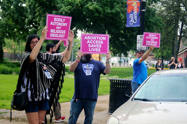 SHEILA SELMAN | THE GOSHEN NEWS<br /> A group of abortion rights supporters hold signs at passing traffic along Main Street in downtown Goshen Saturday evening.