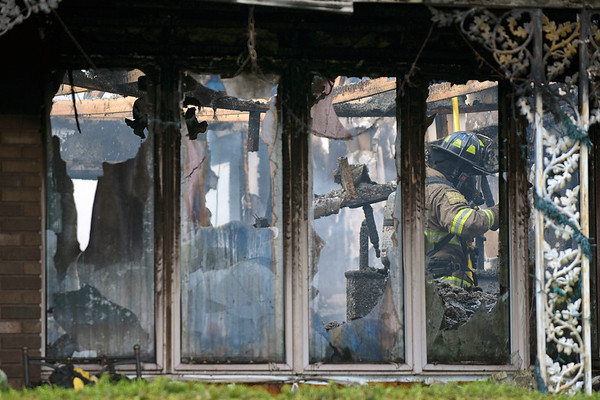 BEN MIKESELL | THE GOSHEN NEWS<br /> A firefighter climbs through rubble inside a burned home Tuesday morning at 12600 C.R. 42 near Millersburg.