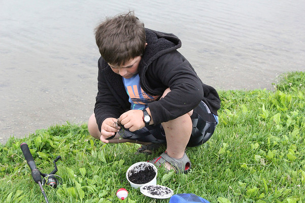 SHEILA SELMAN | THE GOSHEN NEWS<br /> Braydon Miller, Middlebury, baits his hook with a worm at Fidler Pond during the Goshen Parks & Recreation Department's annual Fantastic Fishing Derby.
