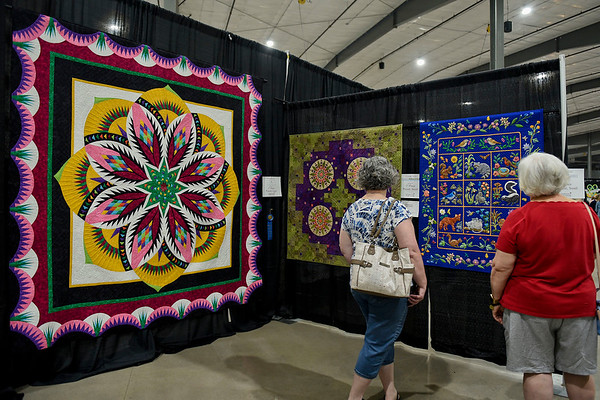 BEN MIKESELL | THE GOSHEN NEWS<br /> Shipshewana Quilt Festival goers browse the quilts on display at the winner's circle during the opening day of the event Wednesday afternoon at the Michiana Event Center in Shipshewana.