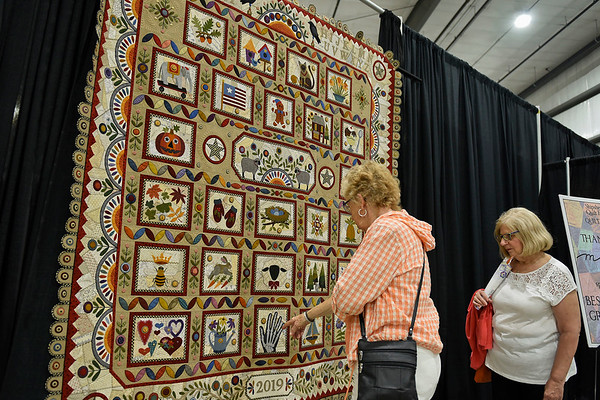 BEN MIKESELL | THE GOSHEN NEWS<br /> Wilma Branson, of Goshen, left, talks with Karen Murphy, of Osceola, Wednesday as they observe a quilt made by Janet Stone, of Overland Park, Kansas, which won the best in show of this year's Shipshewana Quilt Festival in the Michiana Event Center.