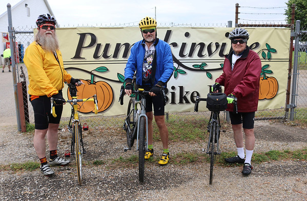 JOHN KLINE | THE GOSHEN NEWS<br /> Keith Konkright, of Scotts, Michigan, left, poses for a photo with his brother, Dan Konkright, of Lynchburg, Virginia, and father, Ottie Konkright, of Battle Creek, Michigan, prior to the kickoff of the 20th annual Pumpkinvine Bike Ride and fundraiser at the Elkhart County 4-H Fairgrounds early Saturday morning.