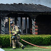 BEN MIKESELL | THE GOSHEN NEWS<br /> Millersburg Clinton firefighter Steve Kuhns carries a pike into a burning house Tuesday morning at 12600 C.R. 42 near Millersburg.