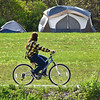 BEN MIKESELL | THE GOSHEN NEWS<br /> A bicyclist drives past the rows of tents May 8 along the Mill Race Trail in Goshen.