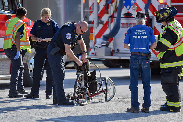 BEN MIKESELL | THE GOSHEN NEWS<br /> Goshen police officers examine the bicycle involved in a crash Friday morning at the intersection of Fifth Street and Lincoln Avenue. The man was treated in an ambulance, but appeared to only have minor scrapes according to witnesses at the scene.