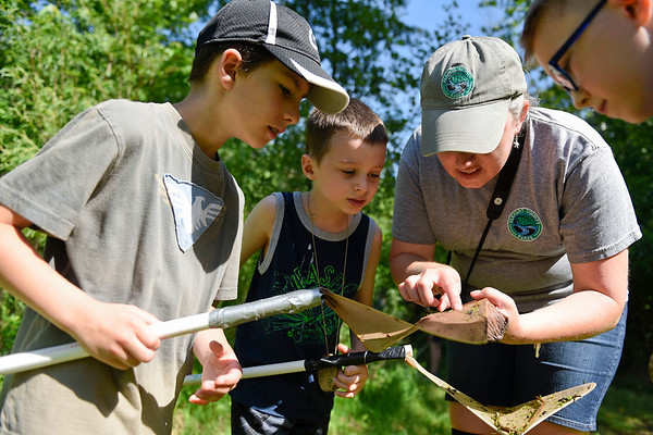 BEN MIKESELL | THE GOSHEN NEWS<br /> August Kumm, 9, of Elkhart, left, stands with Peter Fussner, 7, of Goshen, and naturalist Krista Daniels to check out a baby crawfish he caught Wednesday morning during the Nature Explorers Day Camp at Ox Bow Park.
