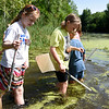 BEN MIKESELL | THE GOSHEN NEWS<br /> Nature Explorer Day Campers wade through high waters looking for bugs and other water critters to scoop up with their nets Wednesday at Ox Bow Park.