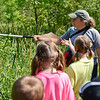 BEN MIKESELL | THE GOSHEN NEWS<br /> On the way to find water critters with their nets, Nature Explorer Day Campers stop to listen to naturalist Krista Daniels as she points out cat tails growing nearby Wednesday in Ox Bow Park.