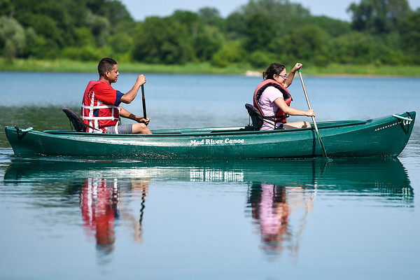 BEN MIKESELL | THE GOSHEN NEWS<br /> Kali Pena, right, paddles through the water with Ivan Diaz, both of Goshen, while they enjoy the warm weather Thursday afternoon at Fidler Pond in Goshen. Temperatures Thursday reached 87 degrees, and today could reach a high of 90, according to the National Weather Service.